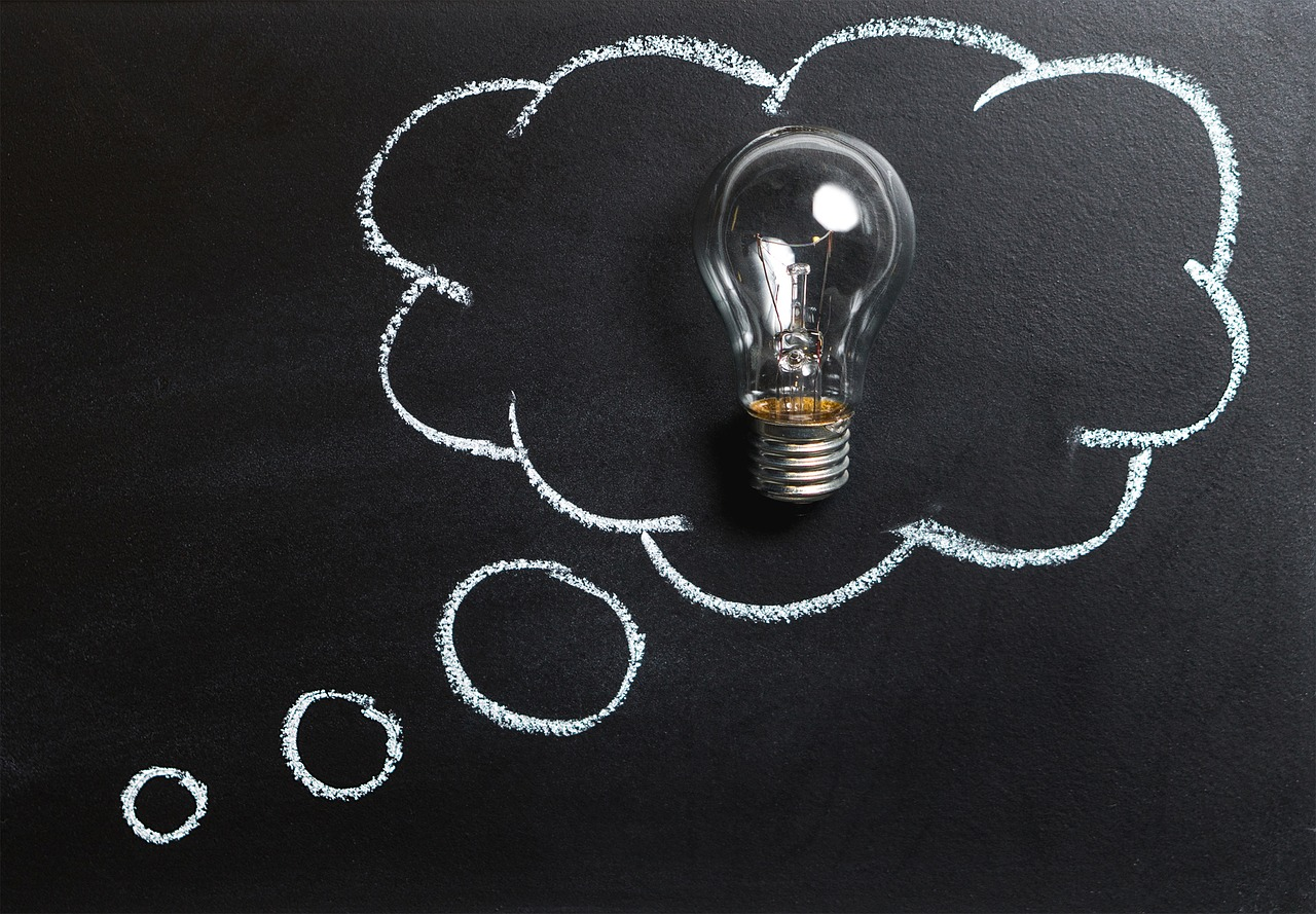Chalkboard background with a thought cloud drawn with a lightbulb inside