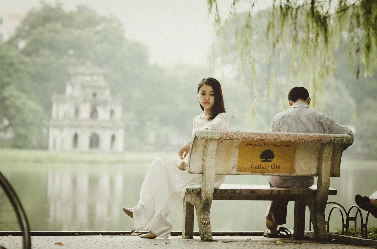 Couple sitting on a bench facing opposite directions