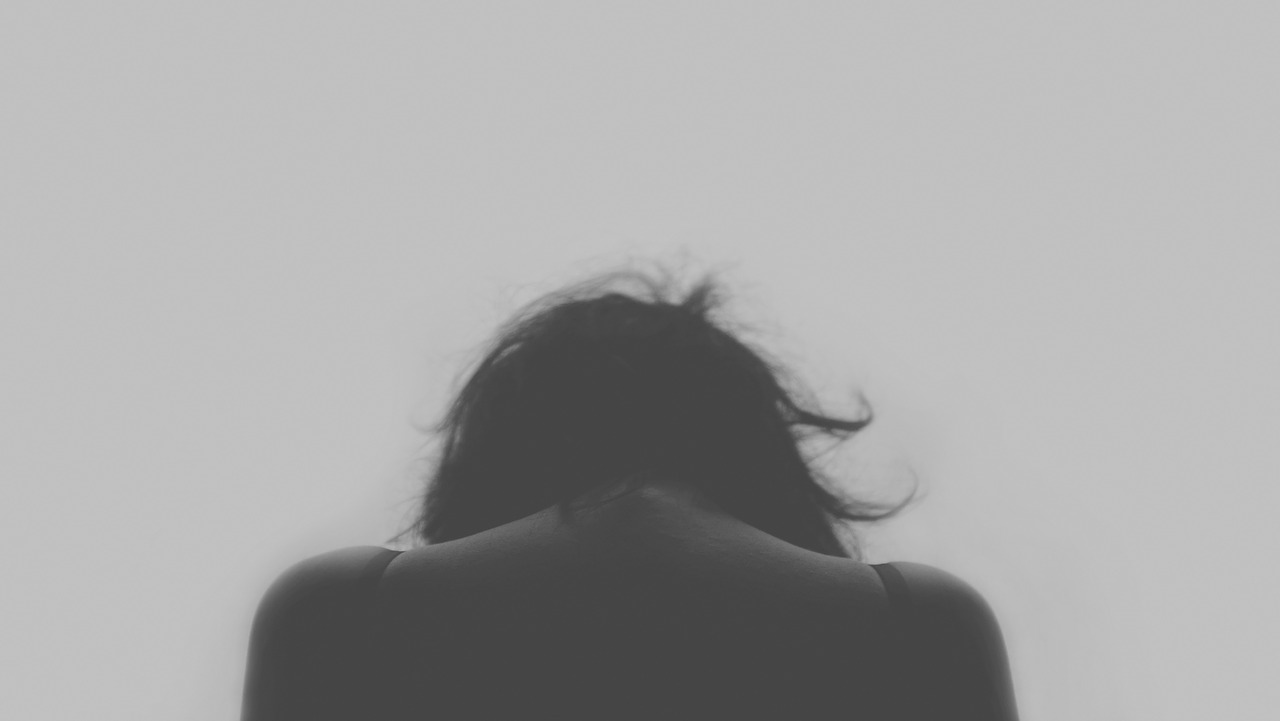 Black and white photo of a woman with her back to the camera and her head hung down