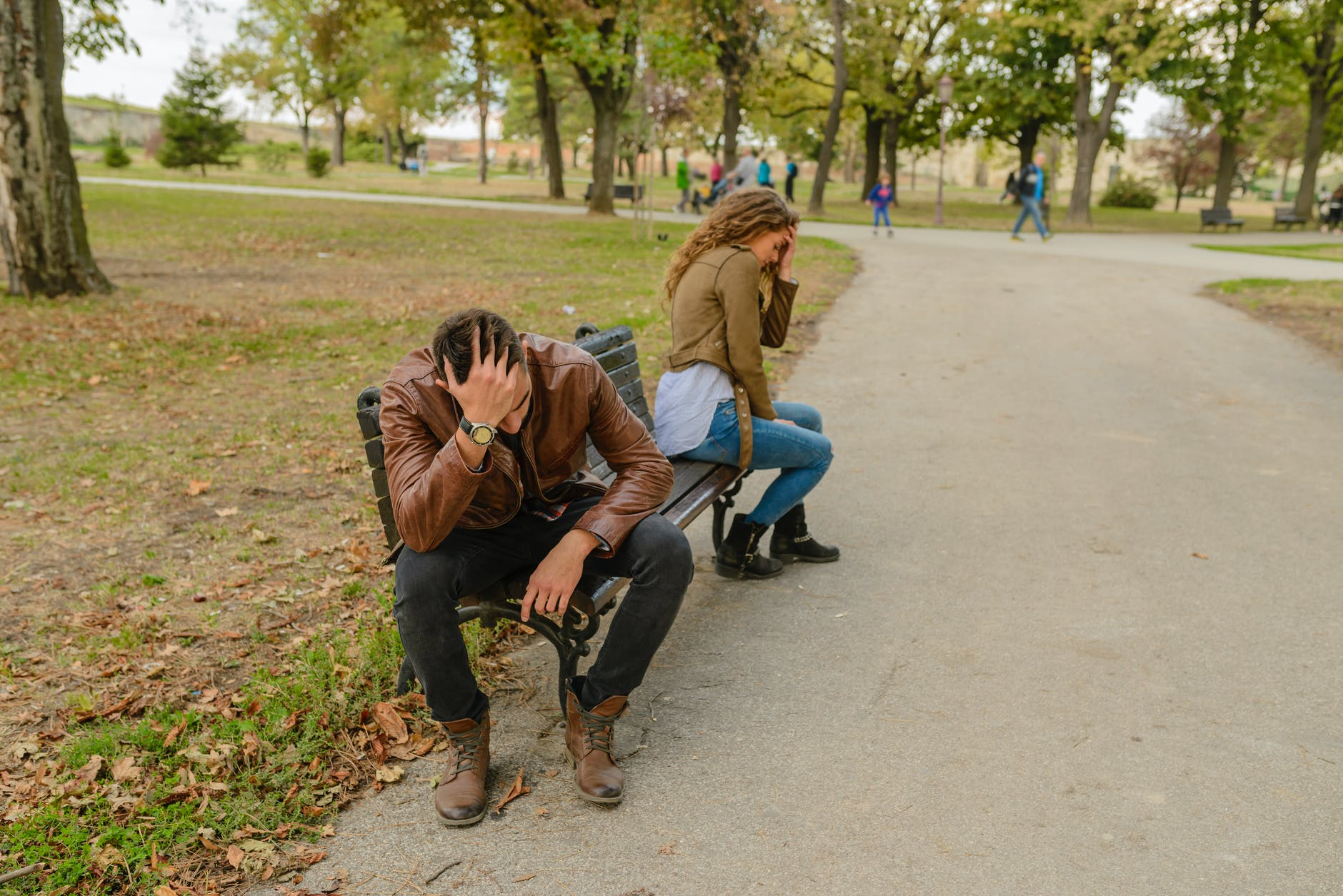 Man and woman sitting apart from each other on park bench looking frustrated