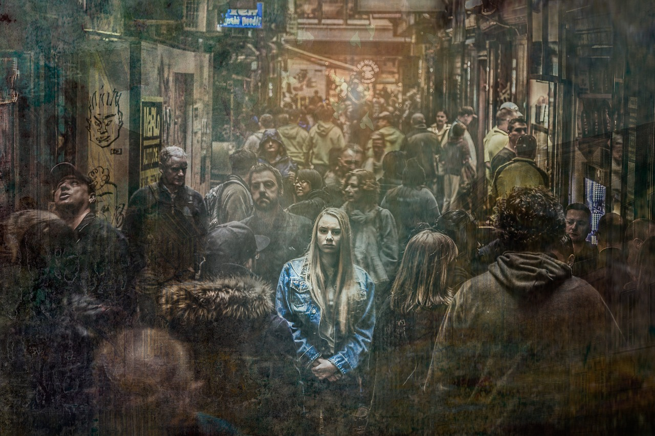 Woman in a crowded alleyway of people facing the camera and highlighted by lighting from above