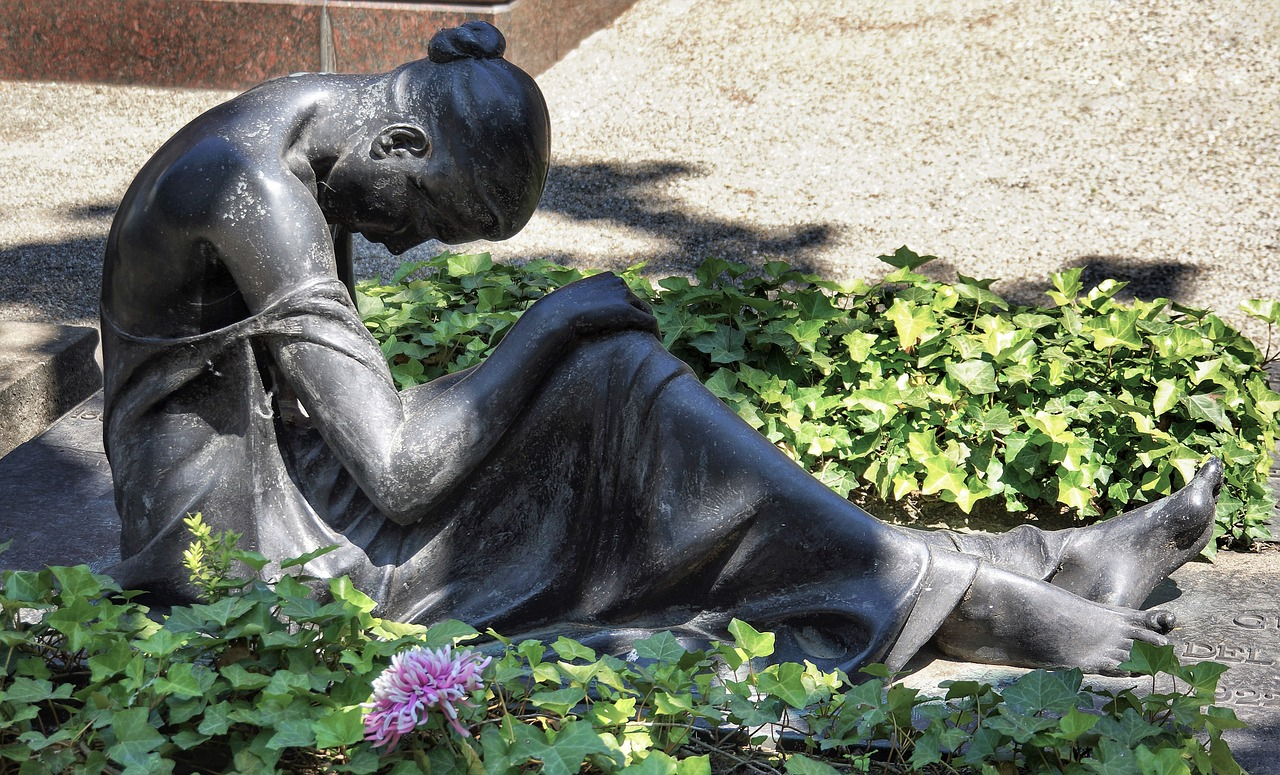 Statue of a woman sitting down with her shoulders and head down in a defeated posture