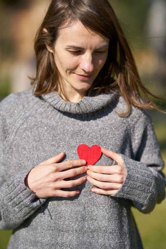 Woman looking down in thought while holding a paper heart to her chest