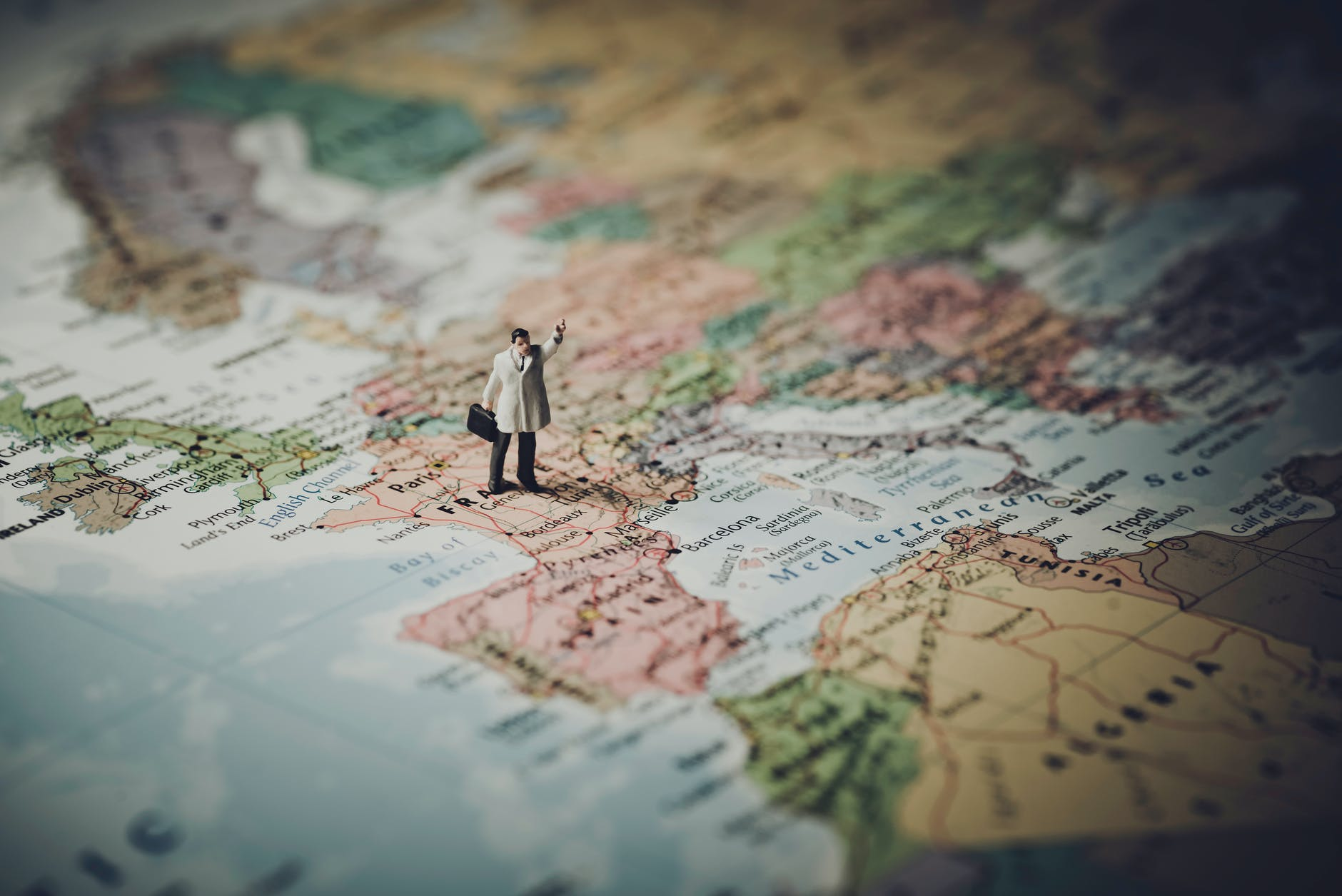 Small figure of a man with a briefcase and hand raised standing on France on a poster of a world map
