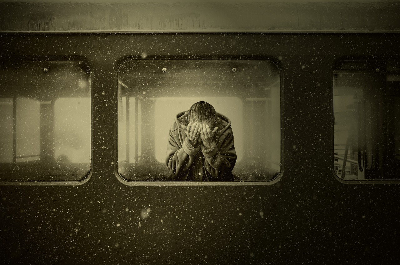 Black and white image of a woman on a train with her head in her hands.