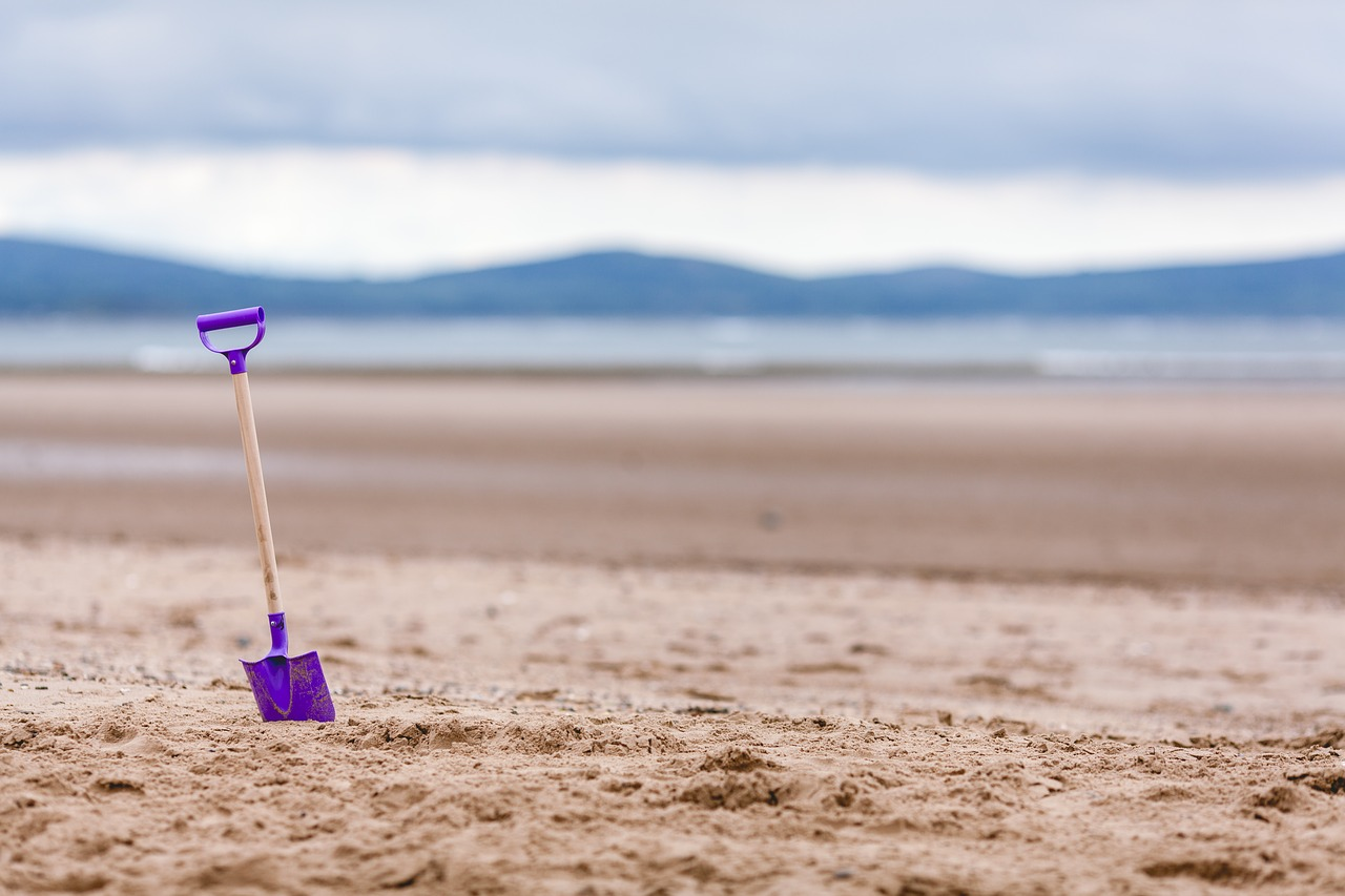 A shovel is stuck in the sand with an unfocused view of the shoreline in the background