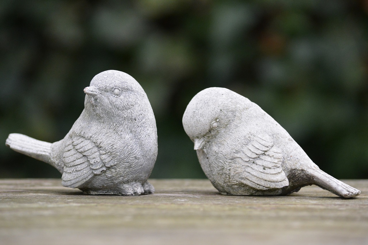 Statue of birds with one looking away and the other with their head hung down