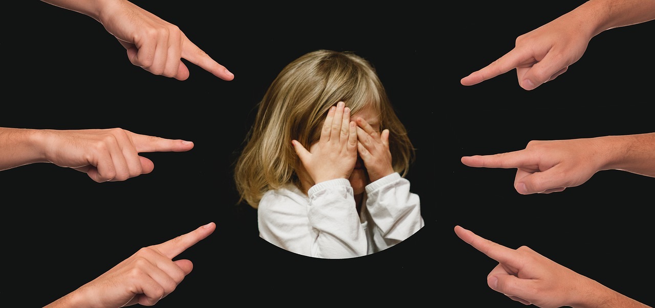 Child covering their face in the center while other hands can be seen pointing at them