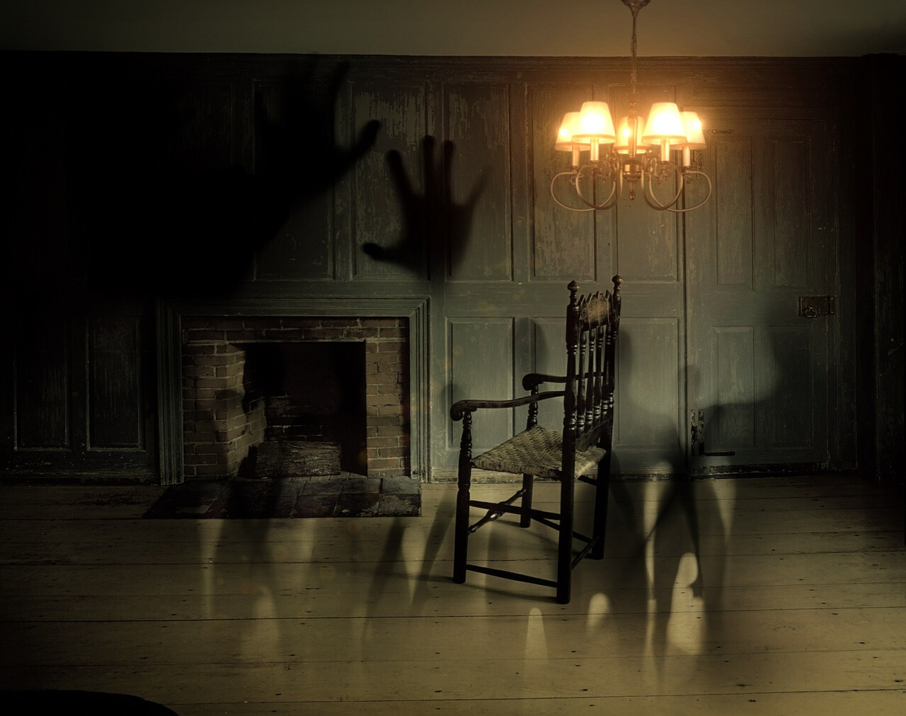 Darkened room with chandelier lit and shadowy figures seen shown on the walls along with larger shadowy hands.