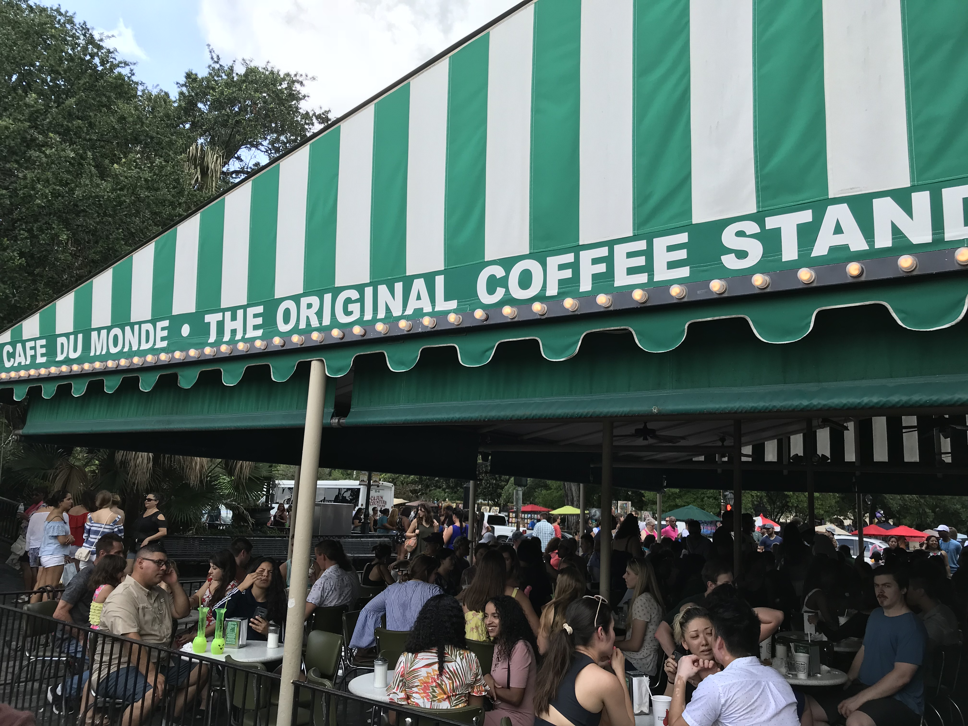 Cafe Du Monde Coffee Stand sign seen over a packed cafe