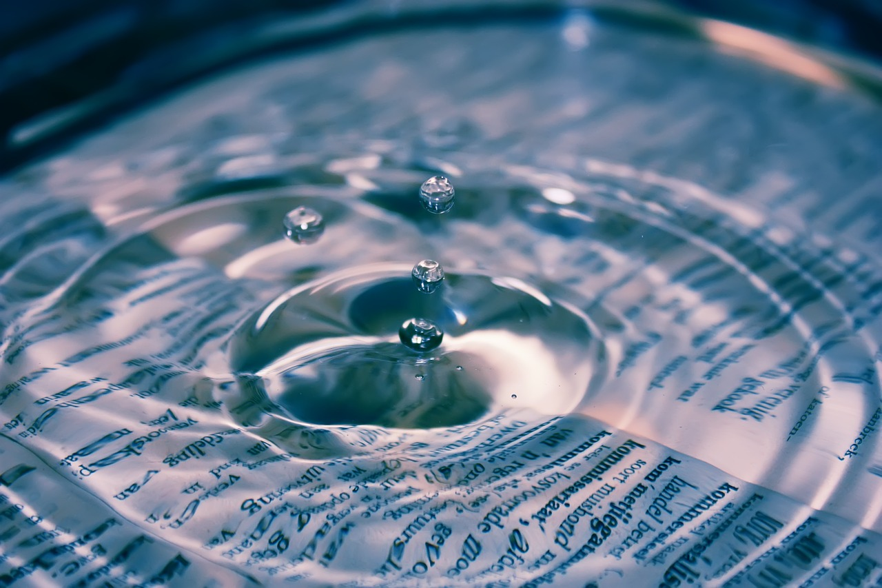 Water droplet into a pool of water covering an open book