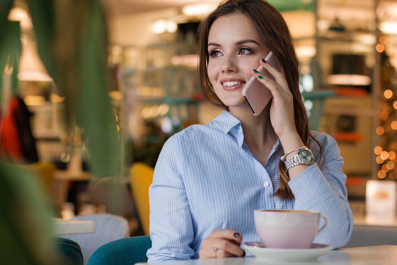 Woman smiling while holding her phone and gazing Into the distance