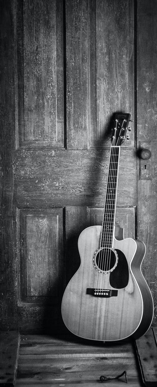 black and white image of a guitar propped against a door