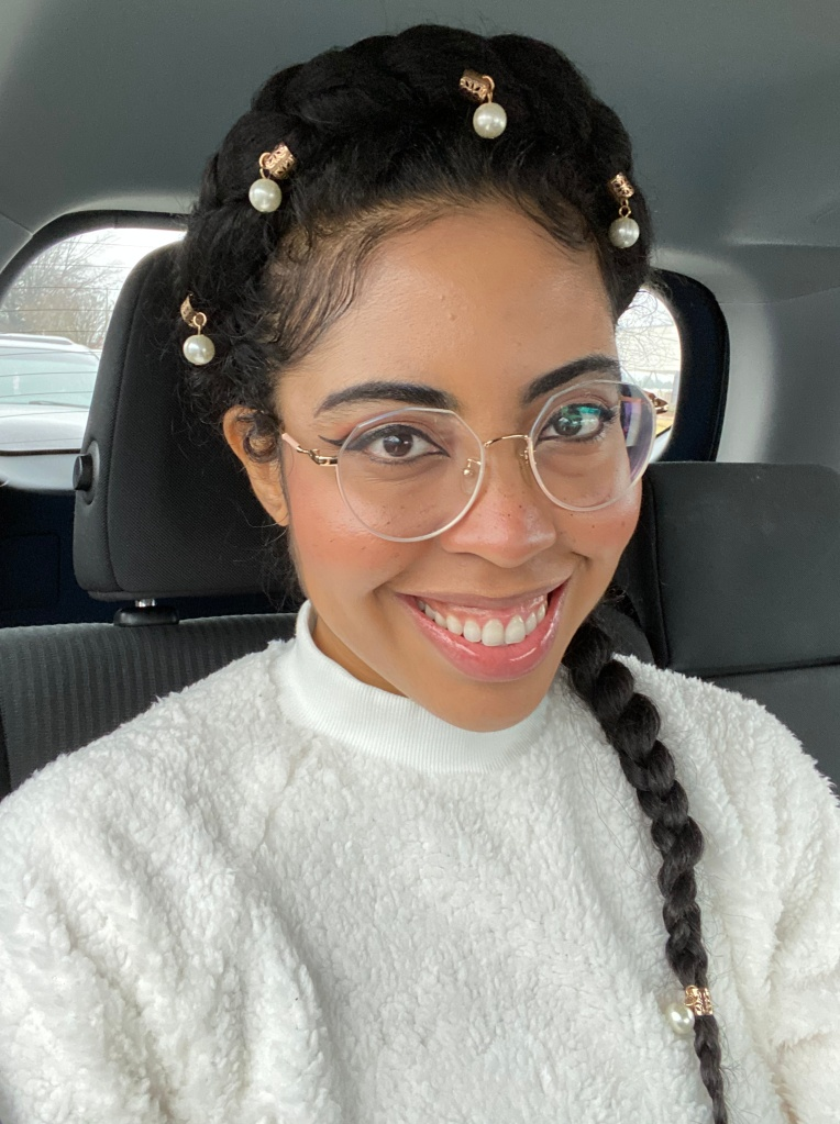 Shep wearing a halo braid hairstyle with pearl decorations along the braid. Clear glasses and a white sweater.