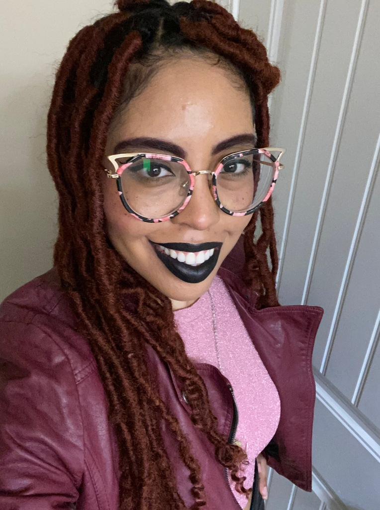 Shep wearing faux loc protective style in red, black lipstick, and cat eye glasses. A pink long sleeve shirt and burgundy leather jacket completes the outfit.